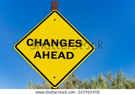 Conceptual Yellow Road Sign on Changes Against Blue Sky - stock photo