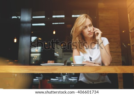 Concerned business woman having unpleasant cell telephone conversation while sitting at the wooden table in coffee shop, attractive upset female calling with smart phone during breakfast in cafe    - stock photo