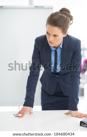 Concerned business woman near flipchart - stock photo