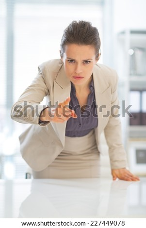 Concerned business woman pointing in camera - stock photo