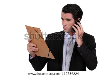 Concerned businessman talking on the phone - stock photo
