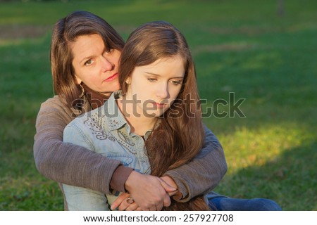 Concerned European mother holding depressed daughter outdoors - stock photo