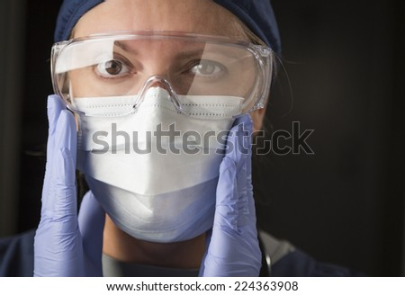 Concerned Female Doctor or Nurse Putting on Protective Facial Wear. - stock photo