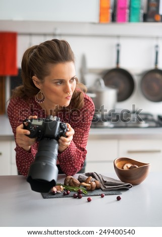 Concerned female food photographer checking photos in camera - stock photo