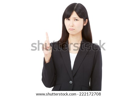 concerned Japanese businesswoman pointing side - stock photo
