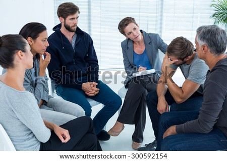 Concerned woman comforting another in rehab group at a therapy session - stock photo
