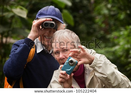 Concerned woman with camera and happy man with binoculars - stock photo