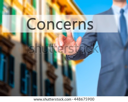 Concerns - Businessman hand touch  button on virtual  screen interface. Business, technology concept. Stock Photo - stock photo