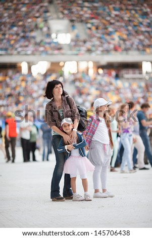 Concert at the stadium. Spectators are on the pitch. Family with two children on foreground - stock photo