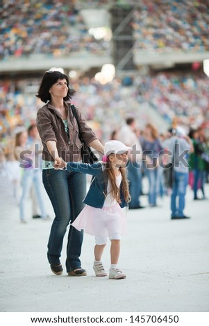 Concert at the stadium. Spectators are on the pitch. Mother dancing with her daughter - stock photo