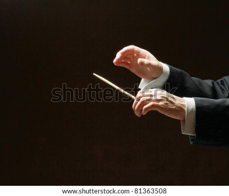 Concert conductor's hands with a baton isolated on a black background