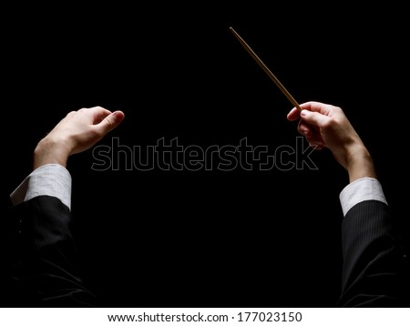Concert conductorwith a baton isolated on a black background, back-view - stock photo