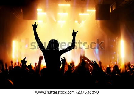 Concert, disco party. Woman silhouette with hands up in foreground and people having fun in night club - stock photo