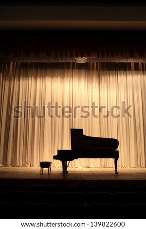 Concert grand piano at theatre stage with brown curtain - stock photo