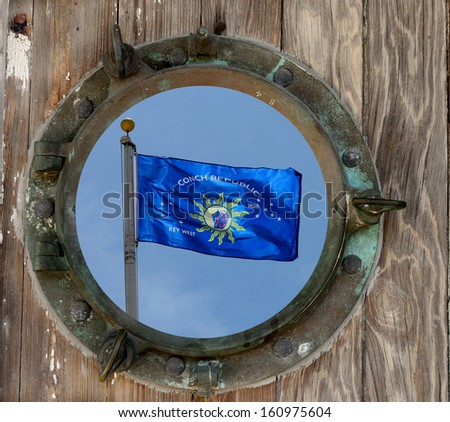 Conch Republic Flag Viewed Through A Rustic Old Porthole. - stock photo