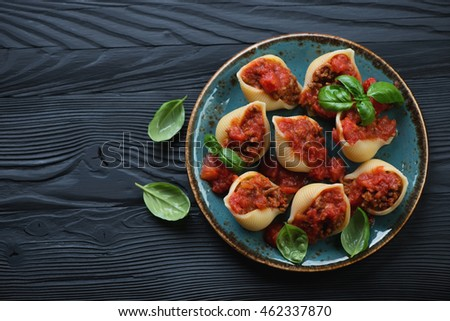 Conchiglioni with minced meat and basil, black wooden background, top view