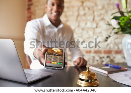 Concierge at hotel reception holds credit card reader to camera - stock photo