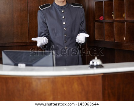 Concierge with empty white gloves behind hotel reception counter - stock photo
