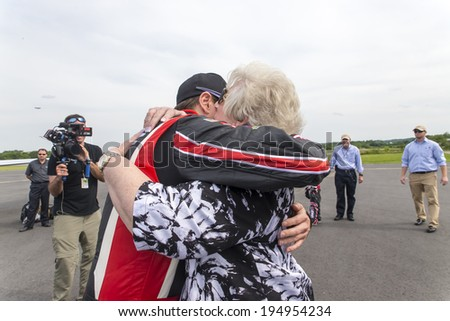 Concord, NC - May 25, 2014:  NASCAR driver, Kurt Busch (26), embraces his family after completing the Indianapolis 500 IndyCar race and landing at Concord Regional Airport in Concord, NC. - stock photo