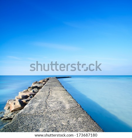 Concrete and rocks pier or jetty on a blue ocean water. Long Exposure photography - stock photo