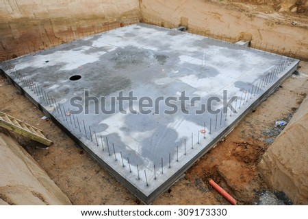 Concrete base in an excavation for a house. - stock photo