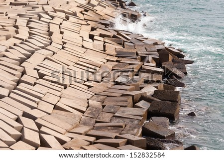 Concrete blocks laid haphazardly forming a protective coastal seawall to prevent erosion from tides and waves as an architectural abstract - stock photo