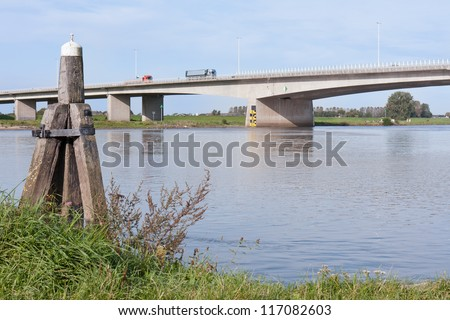 Concrete bridge crossing the river IJssel, the Netherlands, with a wooden bollard in front
