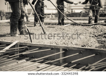 concrete casting work. using concrete vibrator for compacting concrete of stiff consistency. sepia color tone for old feel selection focus to vibration machine. - stock photo