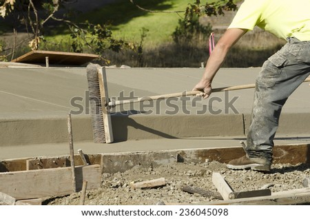 Concrete construction contractor using a broom to install texture in a sidewalk, curb and storm drainage gutter on a new urban road street project - stock photo