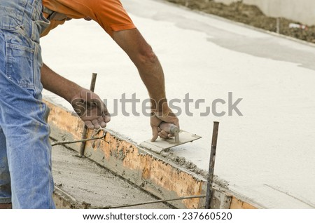 Concrete construction contractor using a edger tool on a sidewalk, curb and storm drainage gutter on a new urban road street project - stock photo