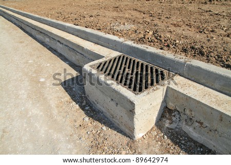 Concrete curb and drainage well at road construction site. The road is ready to be asphalted - stock photo