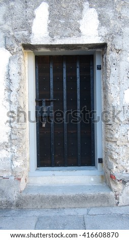 Concrete doorway and locked, old antique wood door with iron reinforcement and iron latch. - stock photo