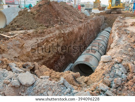 Concrete Drainage Pipe on a Construction Site .Concrete pipe stacked sewage water system aligned on site. - stock photo