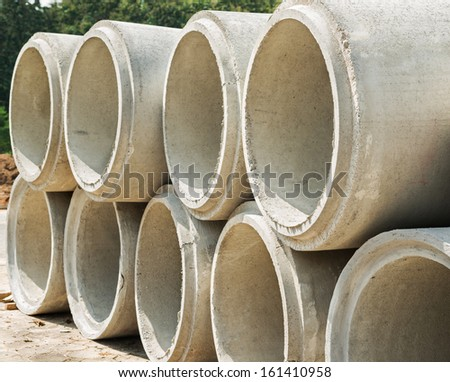 Concrete drainage pipes stacked for building construction  - stock photo