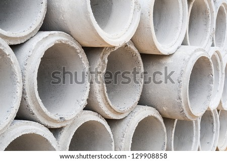 Concrete drainage pipes stacked on construction site - stock photo