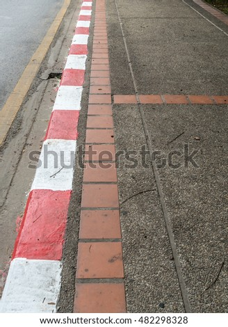 Concrete gravel sidewalk with Red and white concrete curb