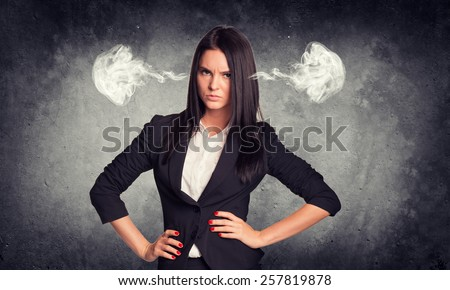 Concrete gray wall with fissure. Wicked woman in suit with steam from ears - stock photo