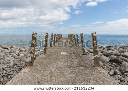 Concrete jetty with fence and ropes - stock photo