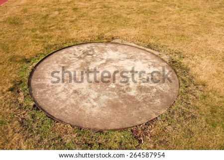 Concrete manhole cover drainage system in the midst of cropped grass - stock photo