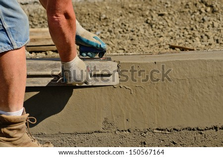 Concrete mason contractor using finishing  trowel at a new commercial residential development project - stock photo