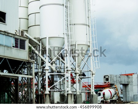 Concrete mixer tower with control station and concrete mixer truck behind in construction site