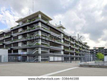 Concrete multi storey parking garage with greenary - stock photo