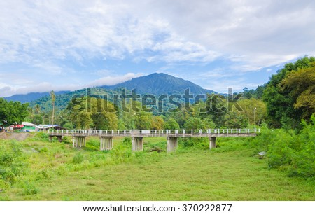 Concrete old bridge, people use for transport and cross. It build among Forrest behind beautiful mountain with blue sky.