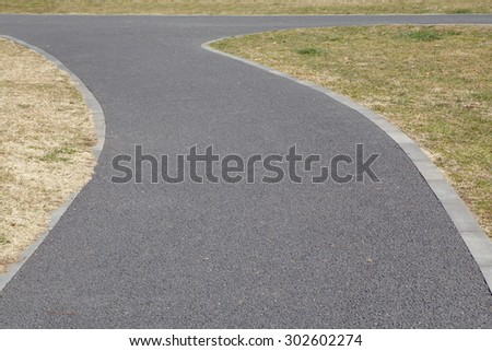 Concrete pathway and green grass at pubic park