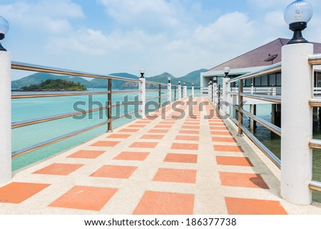 concrete pathway and railing lamp on top pole. the sea is background - stock photo