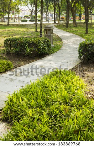 Concrete pathway in public recreation park. - stock photo