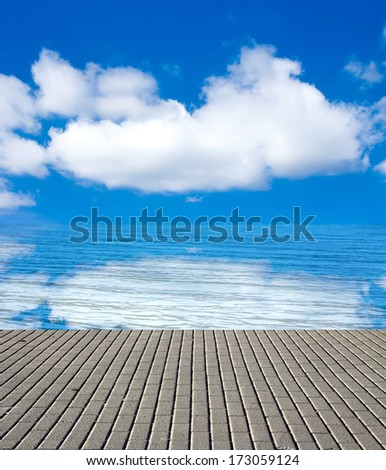 concrete pier on the sea and sky with clouds