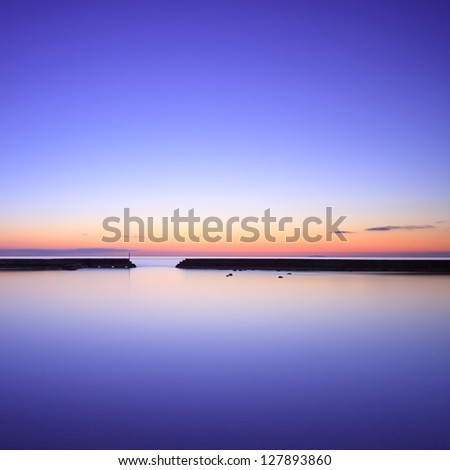 Concrete pier or jetty silhouette and blue ocean on twilight sunset. - stock photo