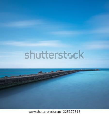 Concrete pier, rocks and sea on sunset. White beach, Tuscany, Italy. Long Exposure. - stock photo