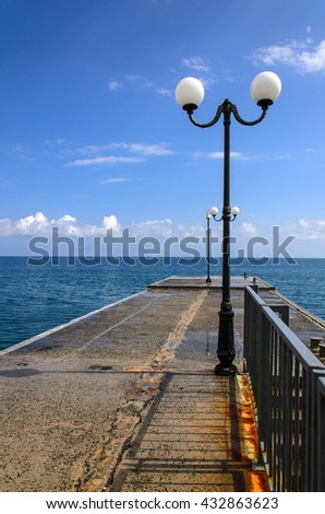 concrete pier with lanterns on sea and sky background